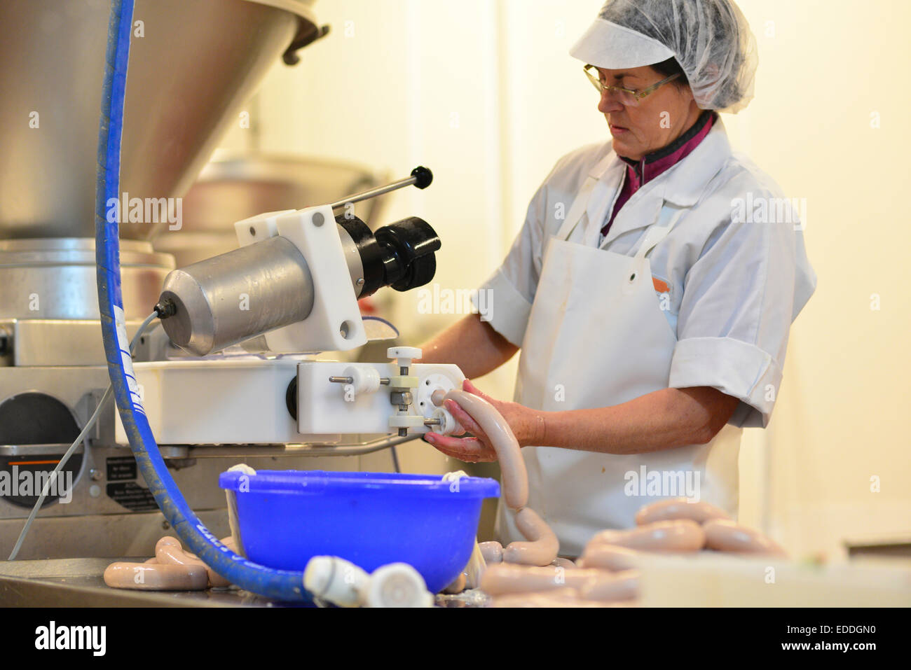 Woman working at sausage production in a butchery - Stock Image
