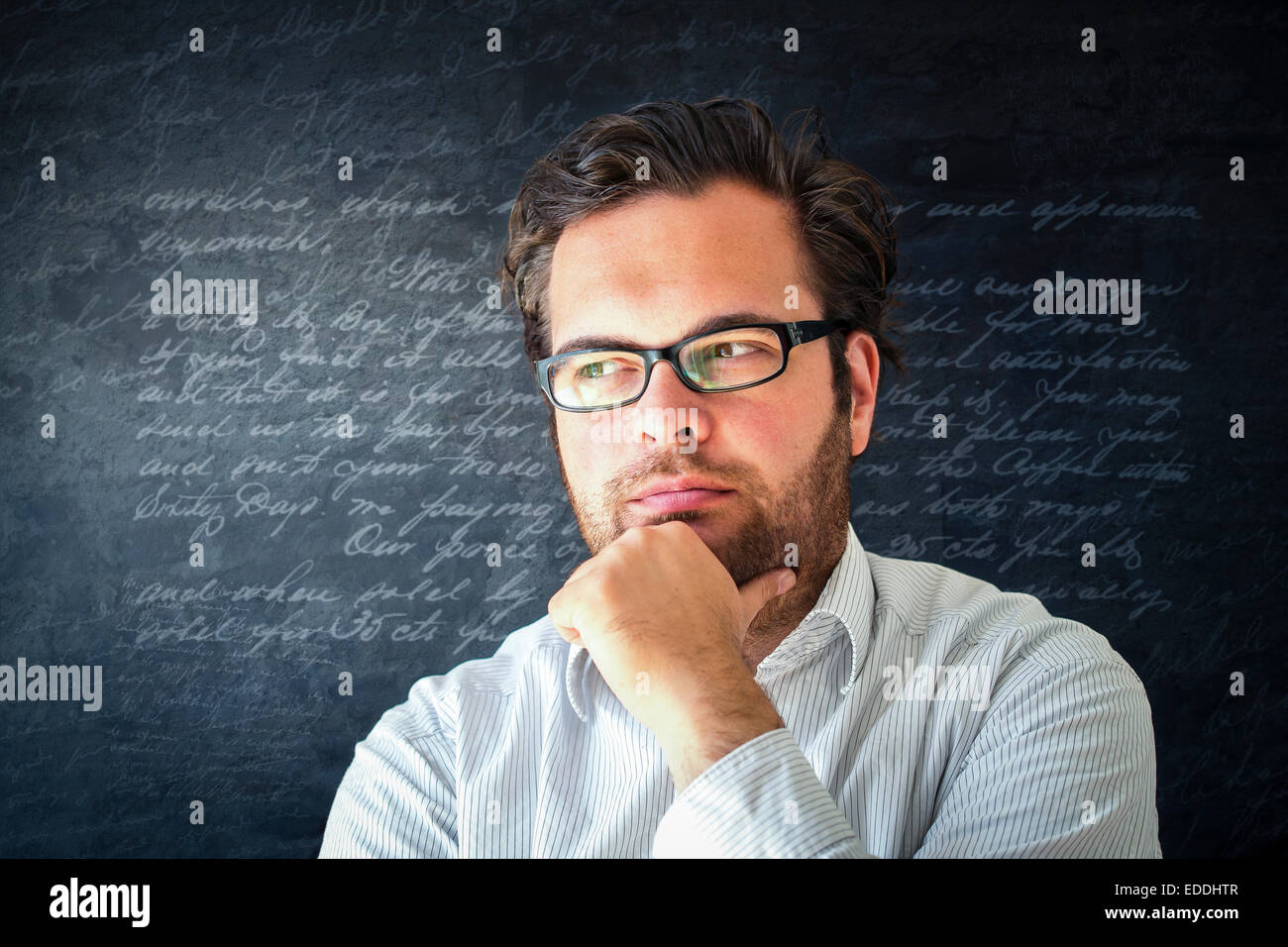 Portrait of pensive man with full beard wearing glasses in front of dark background with writings - Stock Image