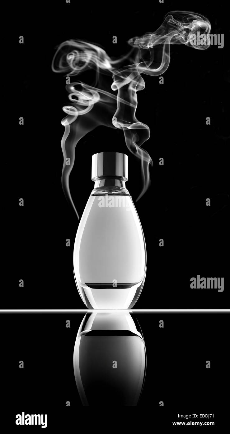 Smoking perfume bottle in front of black background - Stock Image