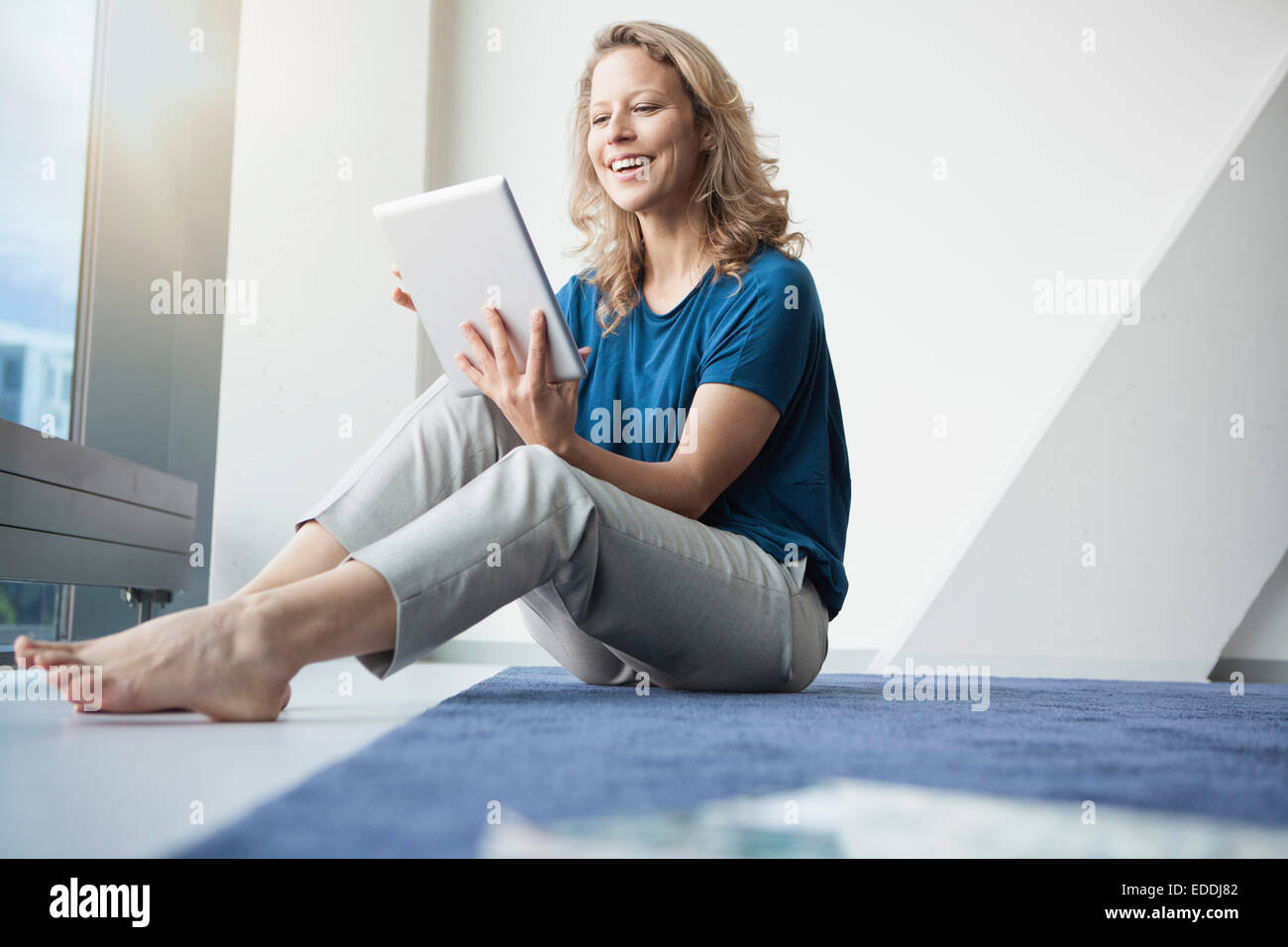 Portrait of smiling mature woman sitting with digital tablet on the floor in her apartment - Stock Image