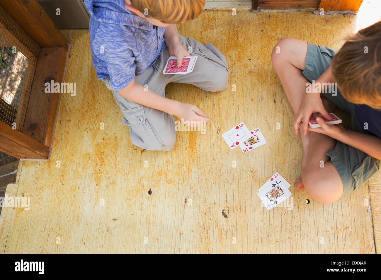 Two brothers playing cards. - Stock Image