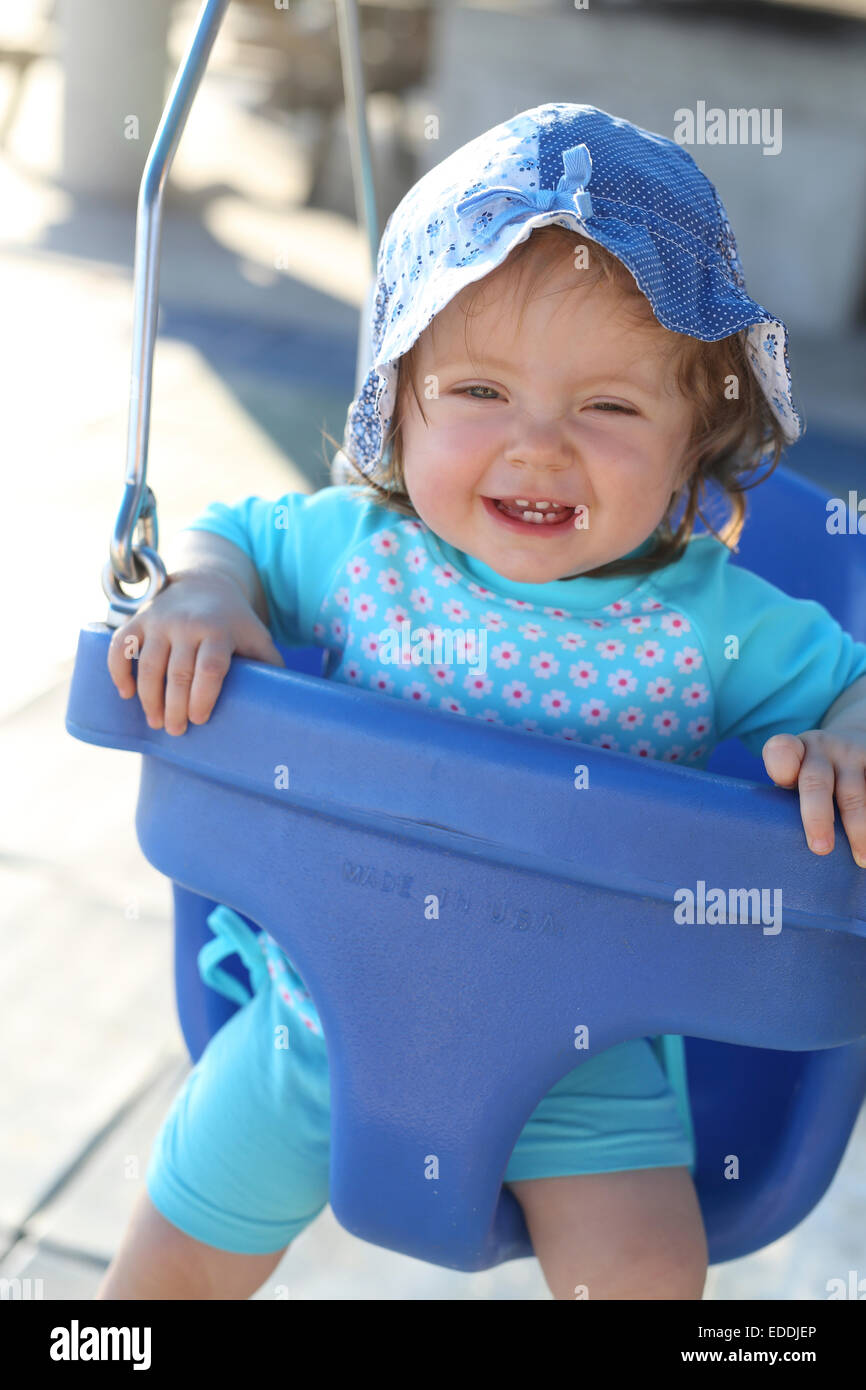 Portrait of smiling baby girl sitting on blue baby swing - Stock Image