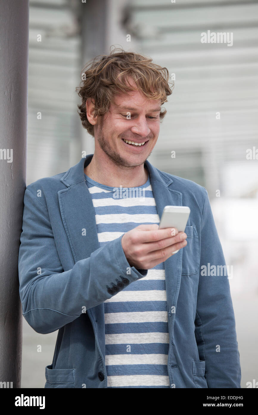 Portrait of smiling man with smartphone reading SMS - Stock Image