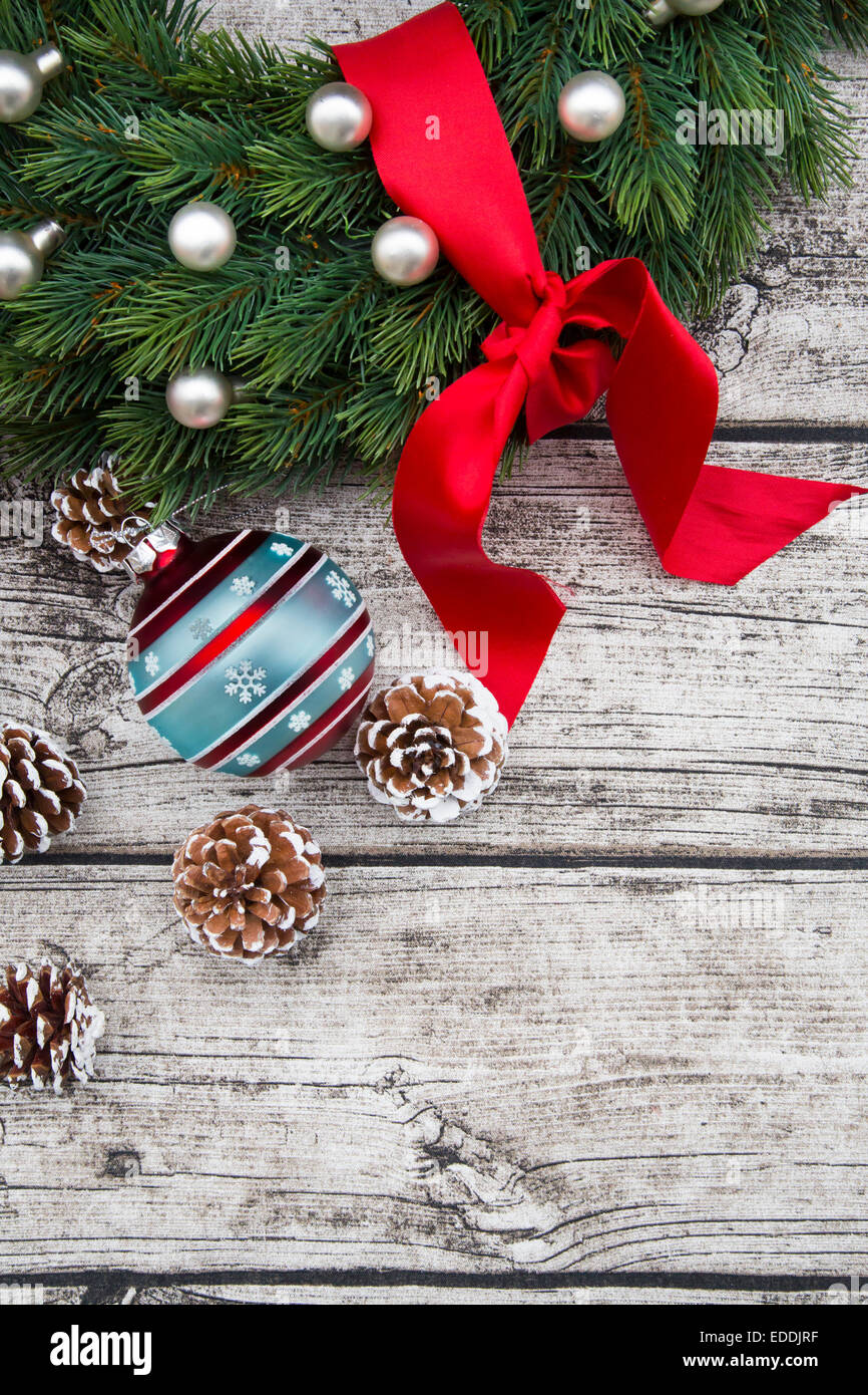 Advent wreath with red bow, Christmas bauble and fir cones on wood - Stock Image
