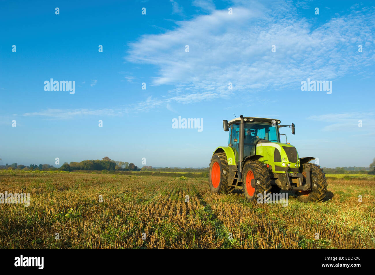 A tractor in a stubble field in Gloucestershire. - Stock Image