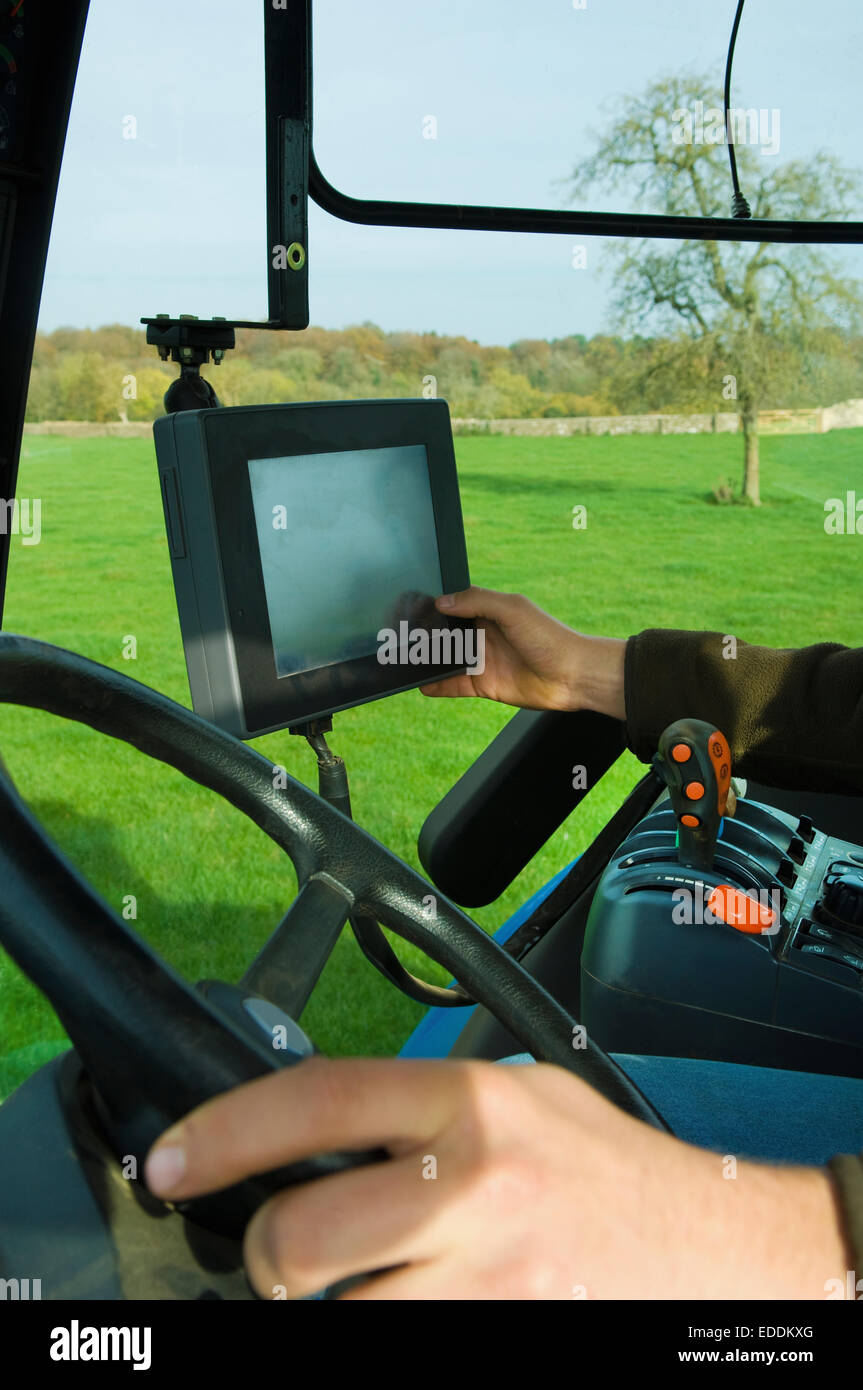 Technical equipment aboard a tractor, a hand touching a touch screen. - Stock Image