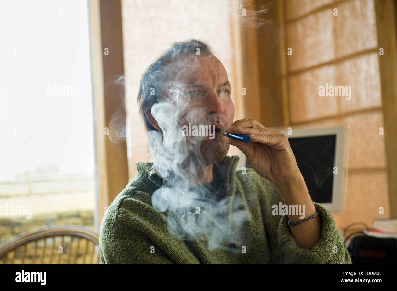 A man using an electronic cigarette, vaping. - Stock Image