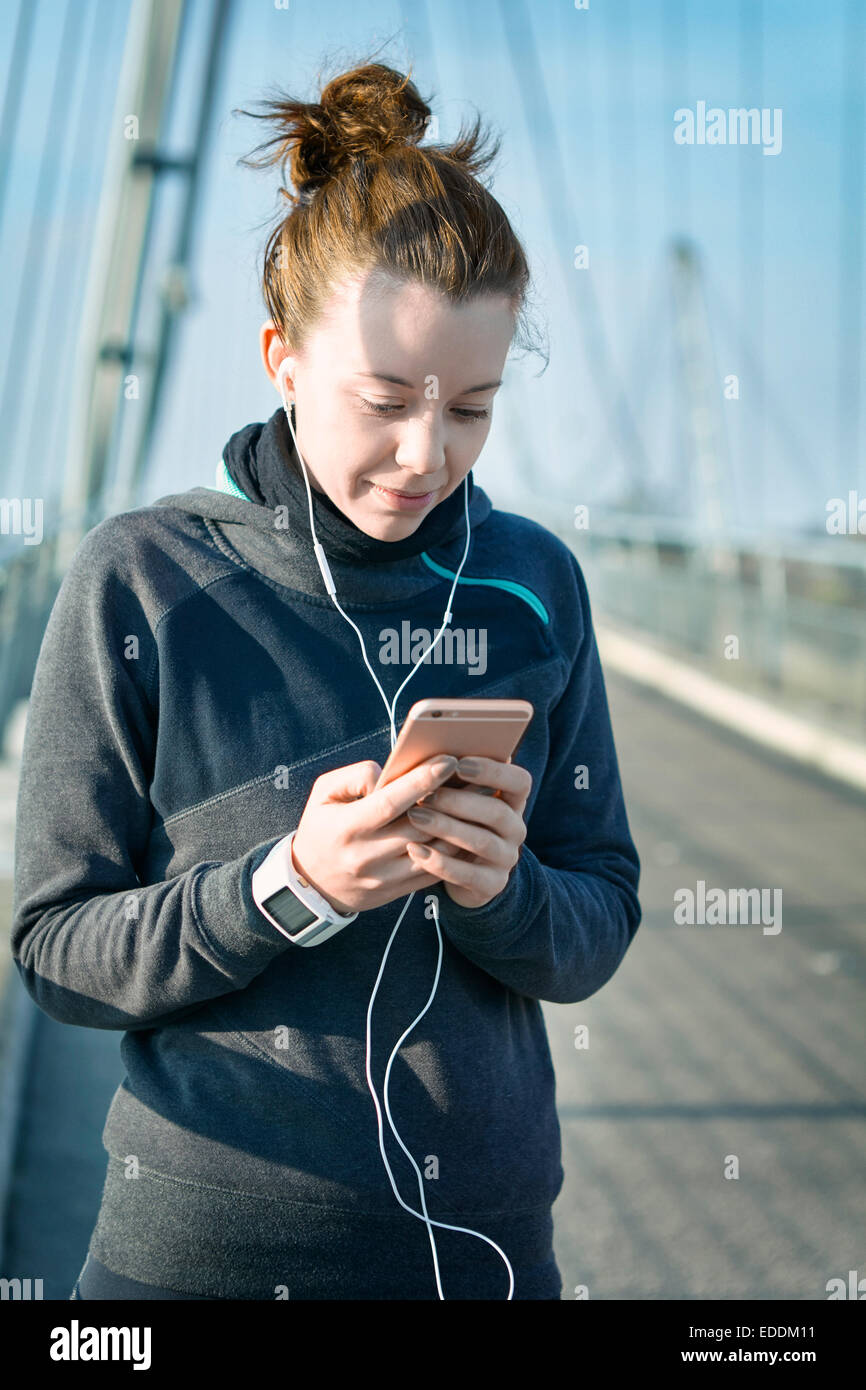 Portrait of young female jogger with heart rate monitor, earphones and smartphone hearing music - Stock Image