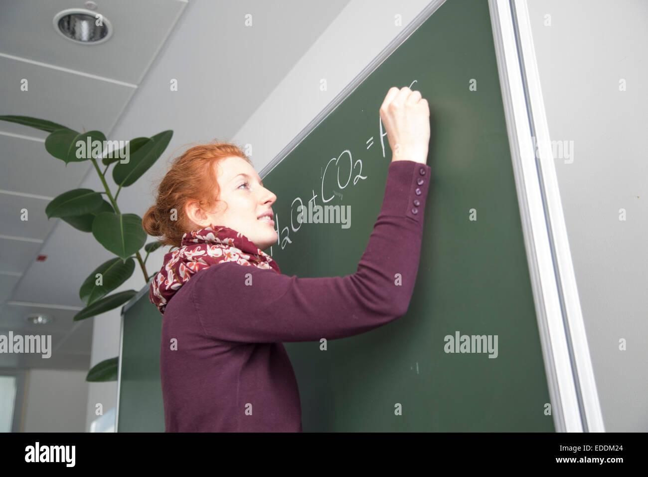 Young female teacher writing formula on blackboard - Stock Image