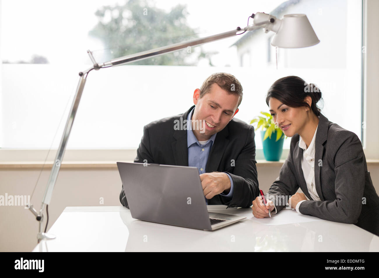 Two business people watching something at laptop - Stock Image