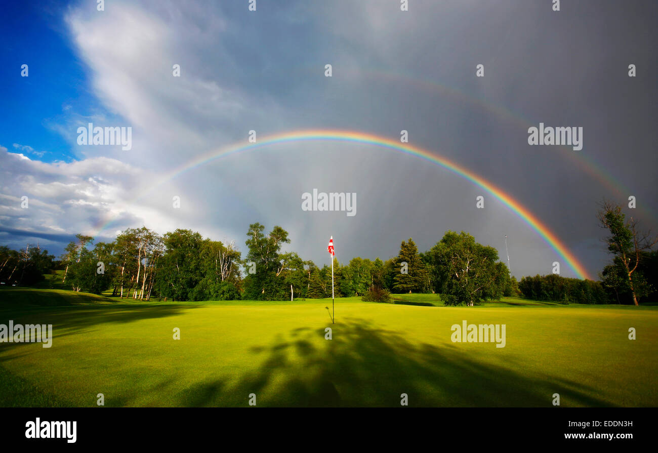 A rainbow in the sky above a golf green. - Stock Image