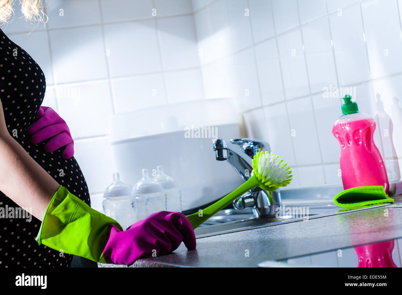 A woman washing up and preparing her milk bottles for expressing in week 30 of her pregnancy. - Stock Image