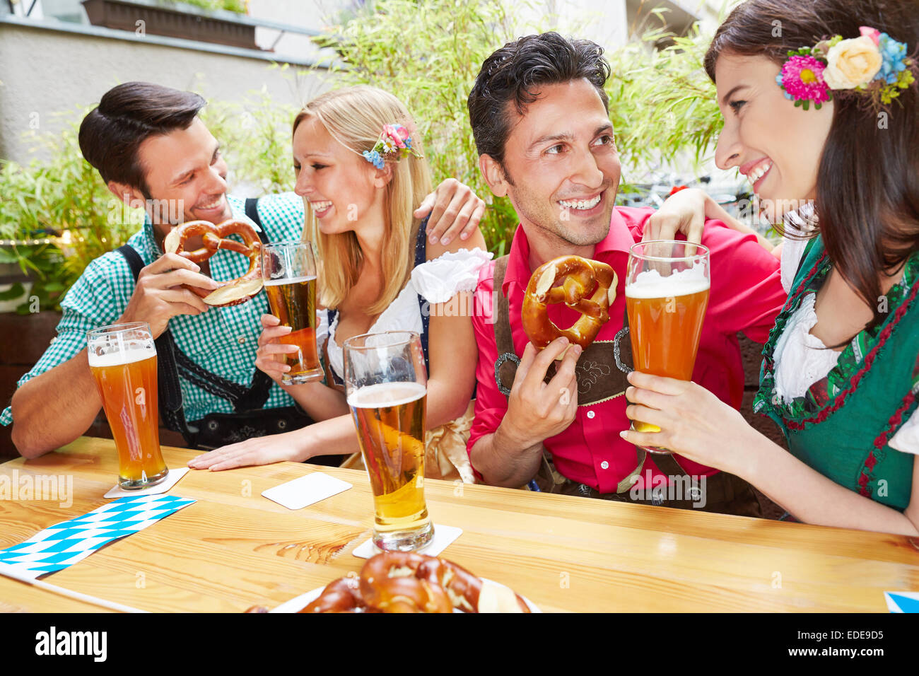 Men and women flirting in bavarian beer garden in summer - Stock Image