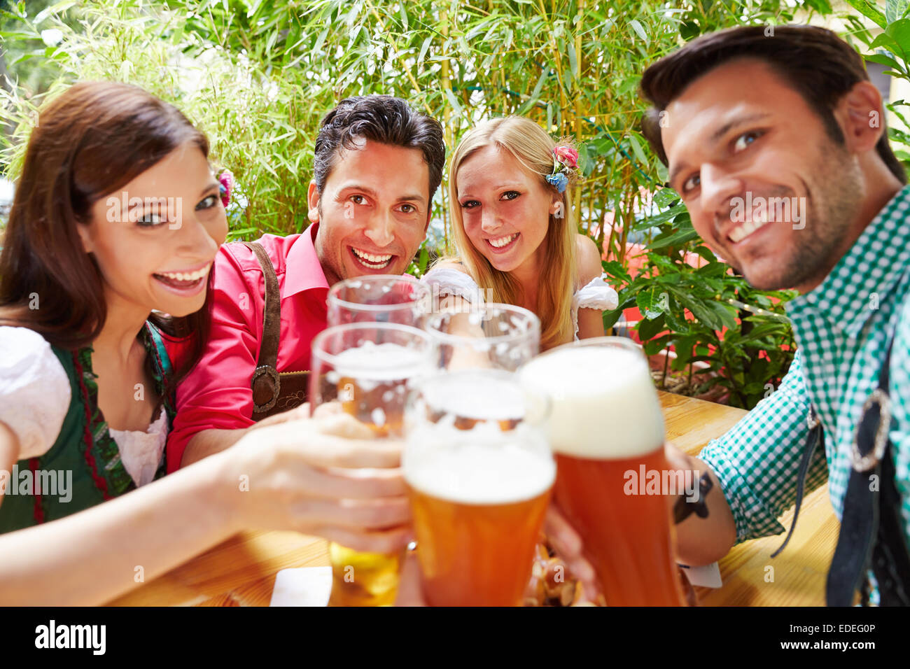 Smiling friends in beer garden clinking their glasses in summer - Stock Image