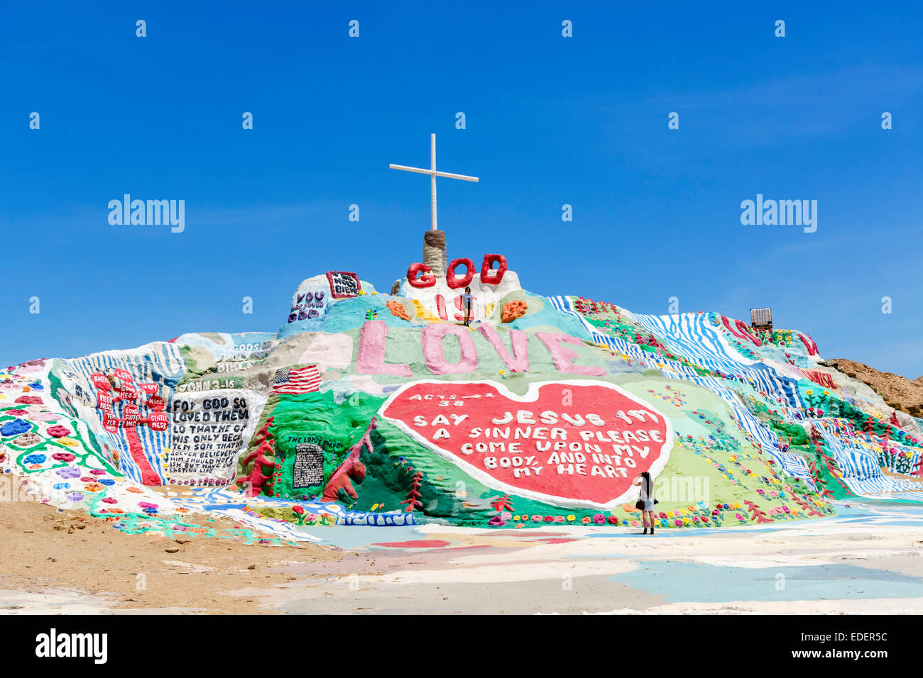 Tourist posing on Salvation Mountain, Leonard Knight's large scale piece of religious folk art, Niland, California, - Stock Image