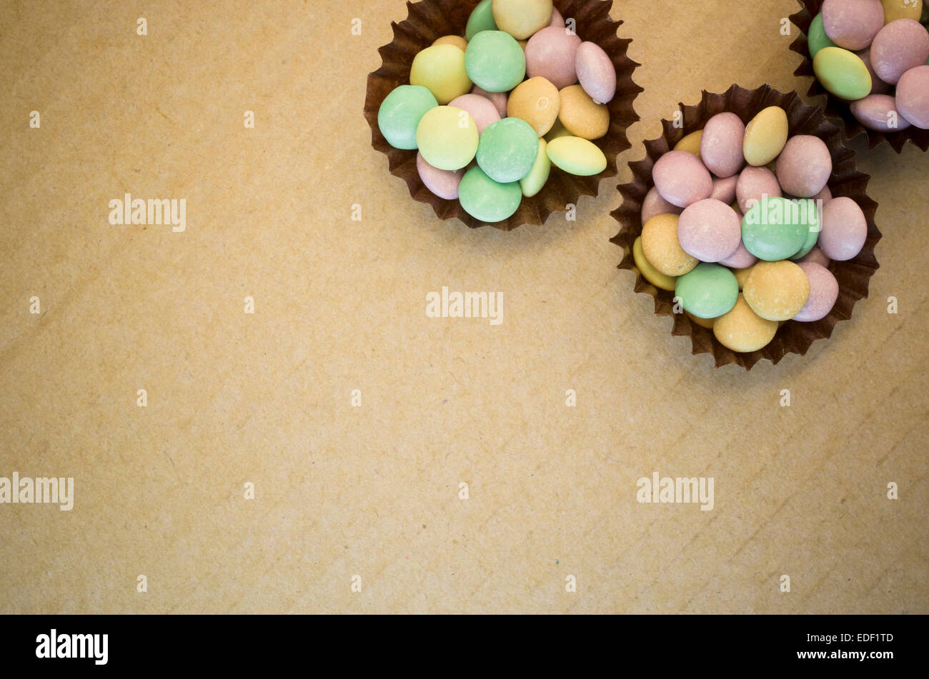 many little colorful sugar bonbons on a paperboard surface - Stock Image