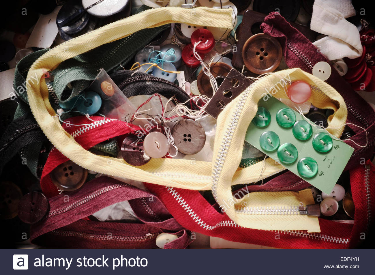 An assortment of mixed zips and buttons for clothing garments. - Stock Image