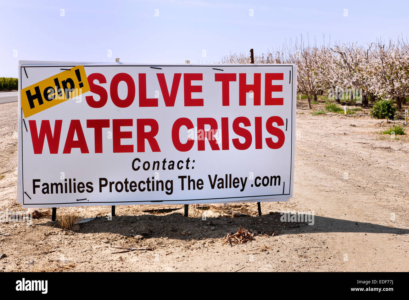 Sign, 'Help!  Solve  The Water Crises'  posted by flowering almond  orchard, - Stock Image