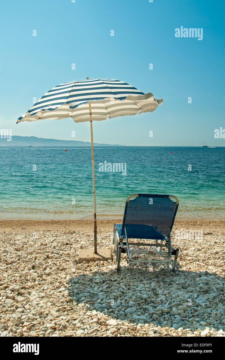 Sunbeds and umbrella on the beach with clear water - Stock Image