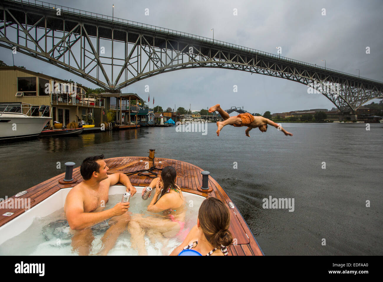 A young man dives off the bow of a hot tub boat in Lake Union during a rain storm. - Stock Image