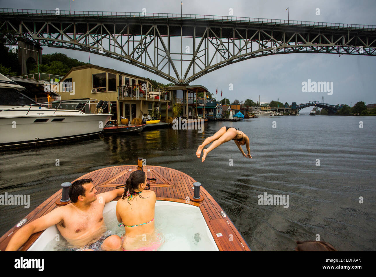 A young woman dives off the bow of a hot tub boat in Lake Union during a rain storm. - Stock Image