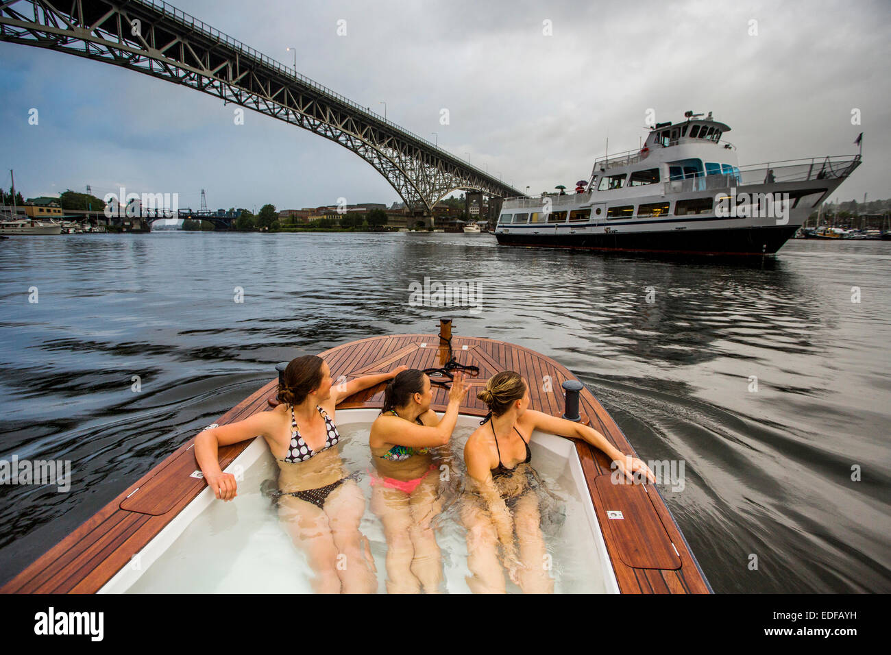 The young women enjoy a hot tub boat in Lake Union while a tour boat cruises along the calm waters. - Stock Image