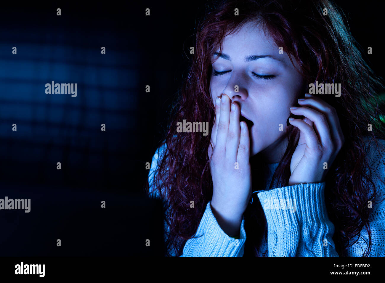 Yawning Woman Working on a Computer with Headset at Night Stock Photo