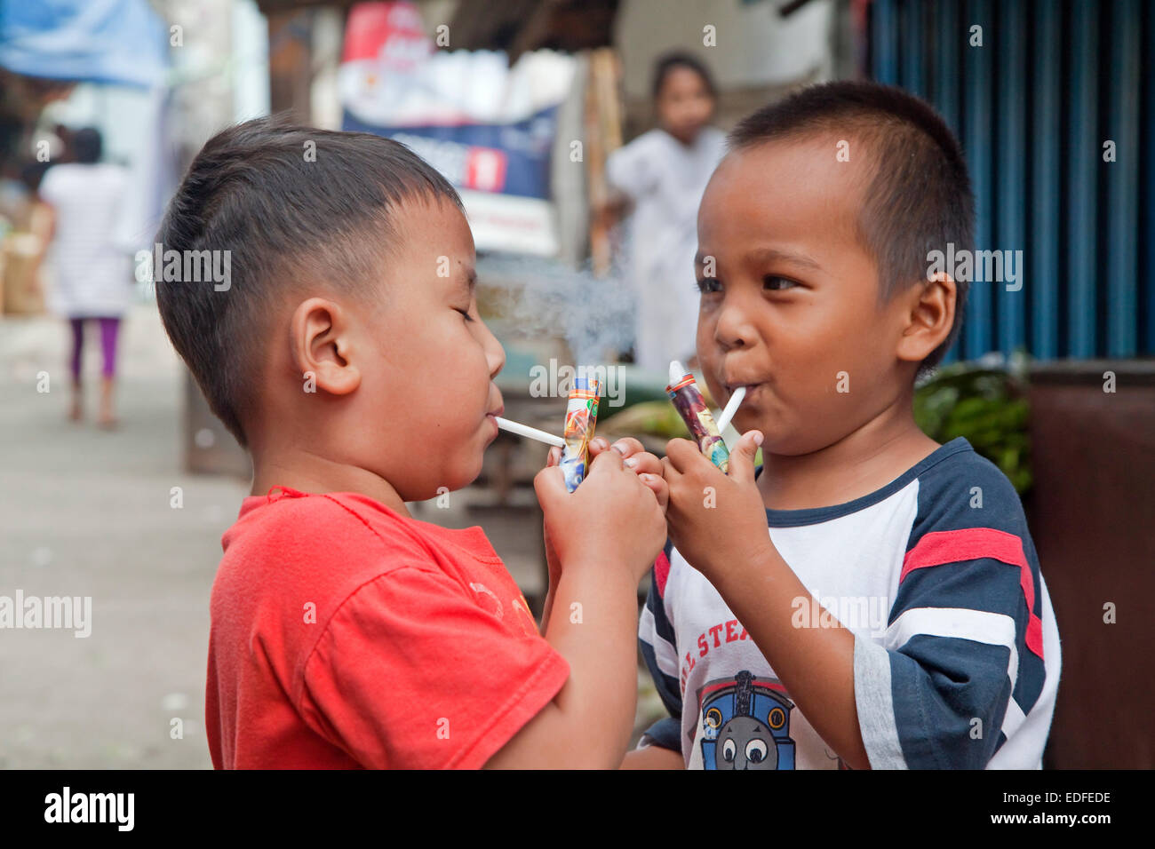 Indonesian children being taught how to smoke by being allowed to puff away on home-made pipes called Popeye Lauts, - Stock Image