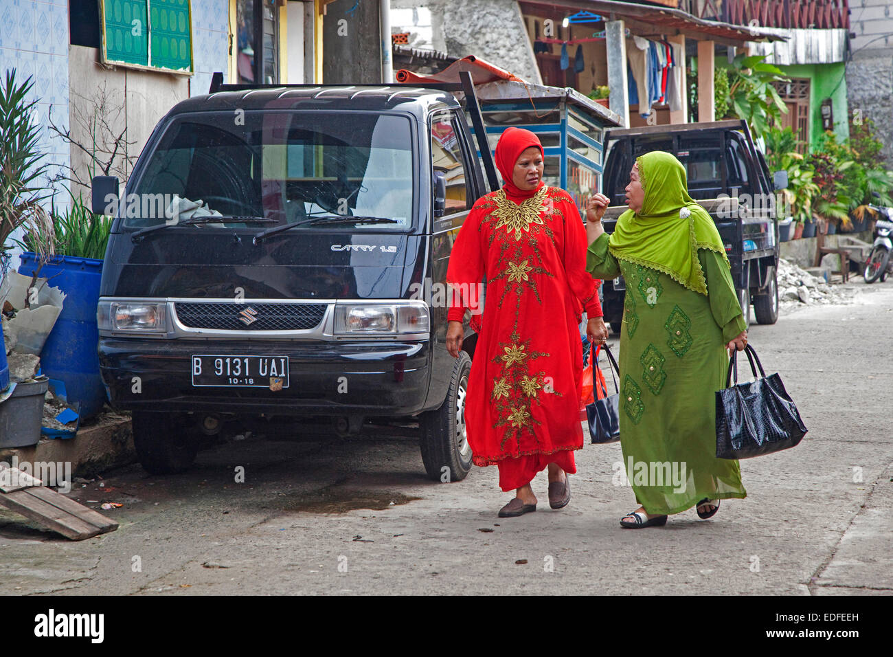 Two Muslim women wearing brightly coloured kerudung and Islamic hijab dress in Kota / Old Batavia, Java, Indonesia - Stock Image