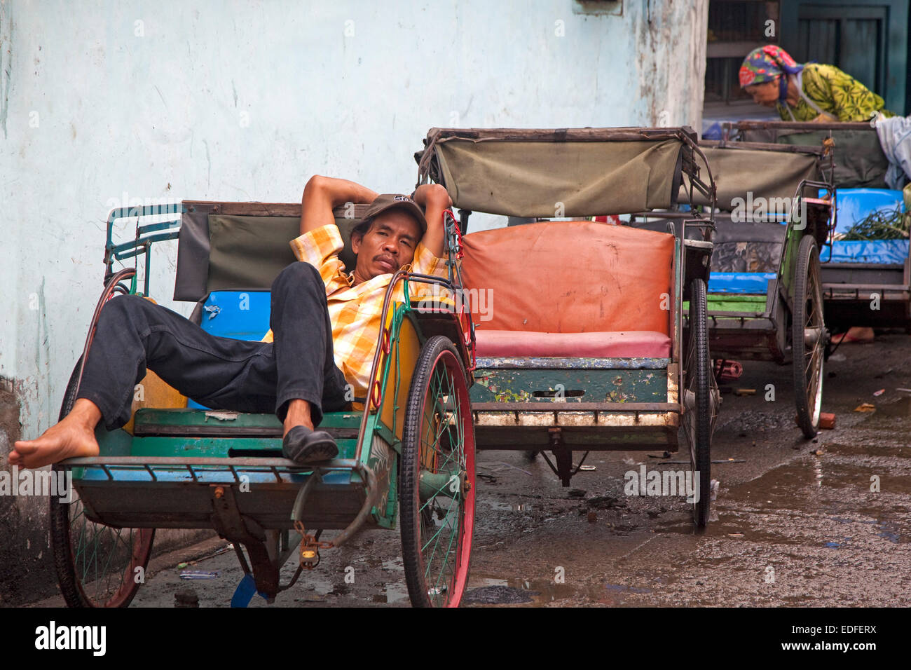 Indonesian becak driver waiting for clients in his cycle rickshaw, Jakarta, Java, Indonesia - Stock Image