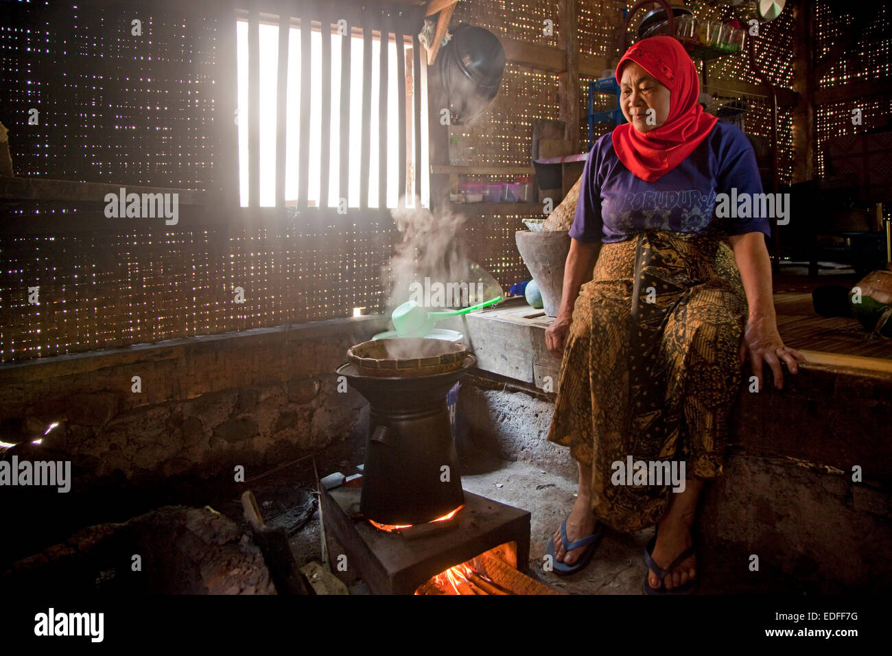 Indonesian elderly, woman cooking rice in traditional bamboo house, Cianjur Regency, West Java, Indonesia - Stock Image