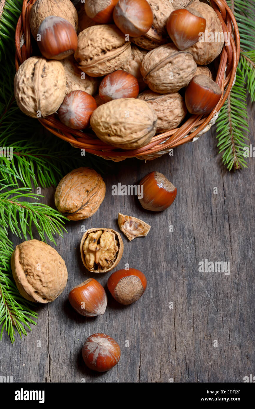 Walnuts and hazelnuts in  bowl isolated on old wooden background - Stock Image