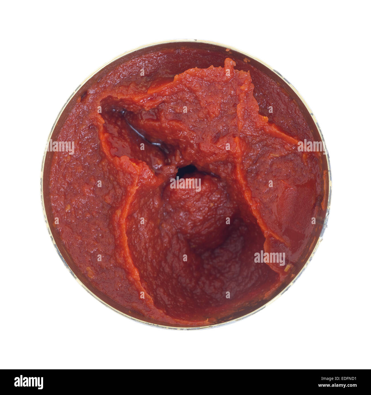 Top view of an opened can of tomato paste on a white background. - Stock Image