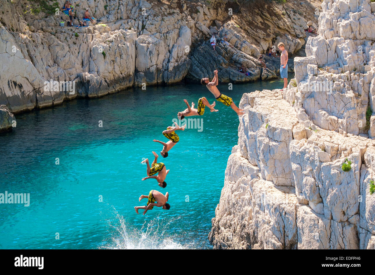 Miltiple exposure composite image of man doing a backflip from a rocky outcrop at Calanque de Sugiton - Stock Image