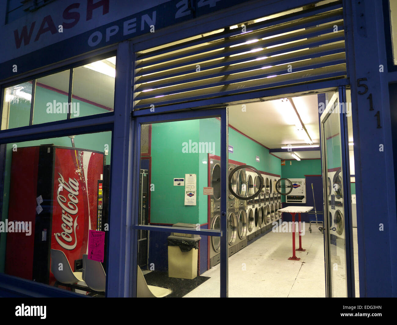 Typical small town American Laundromat coin wash laundry interior & Coca Cola machine at night in Pacific Grove - Stock Image