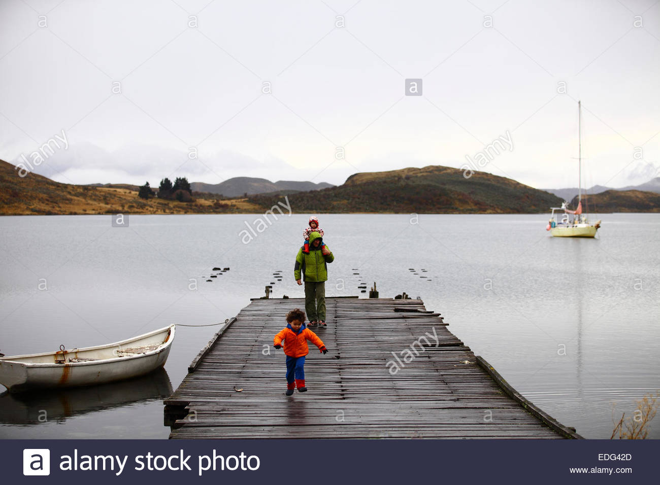 A father walks along an old pier used by Pesca Chile in the Eberhard fjord, near Puerto Prat, Chile. - Stock Image