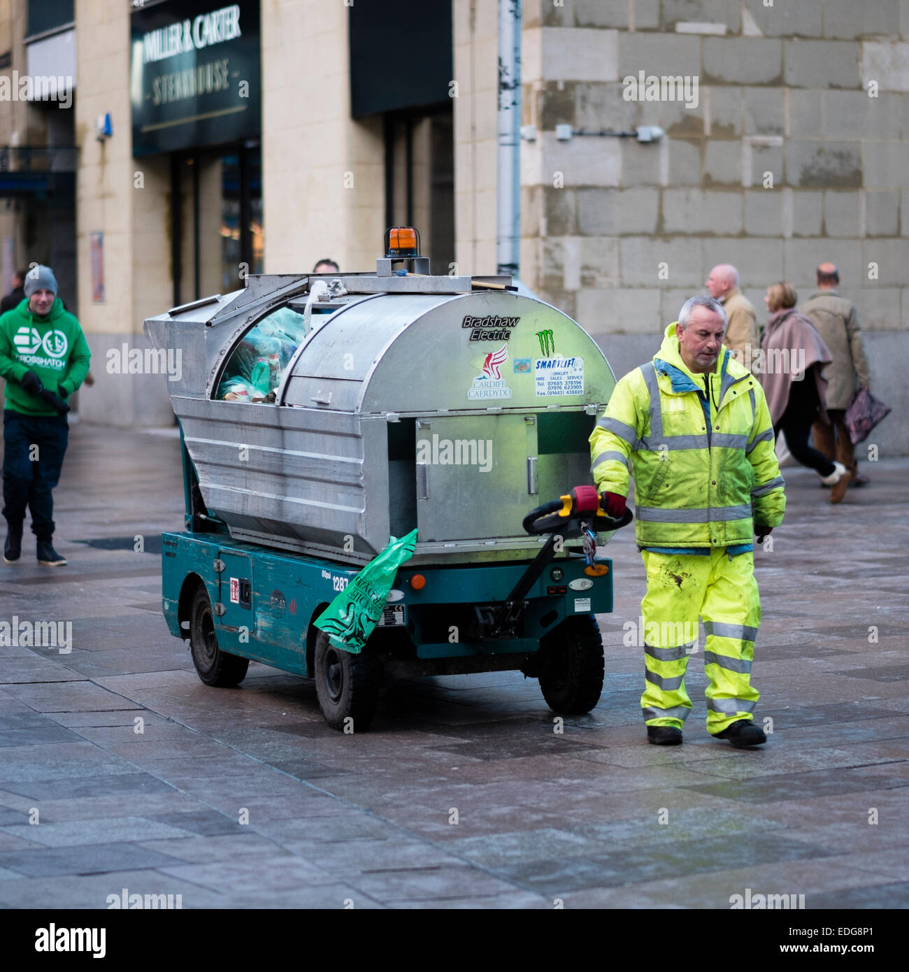 A street cleaner working pulling an electric rubbish cart trolley in Cardiff city centre, the Capital of Wales UK Stock Photo