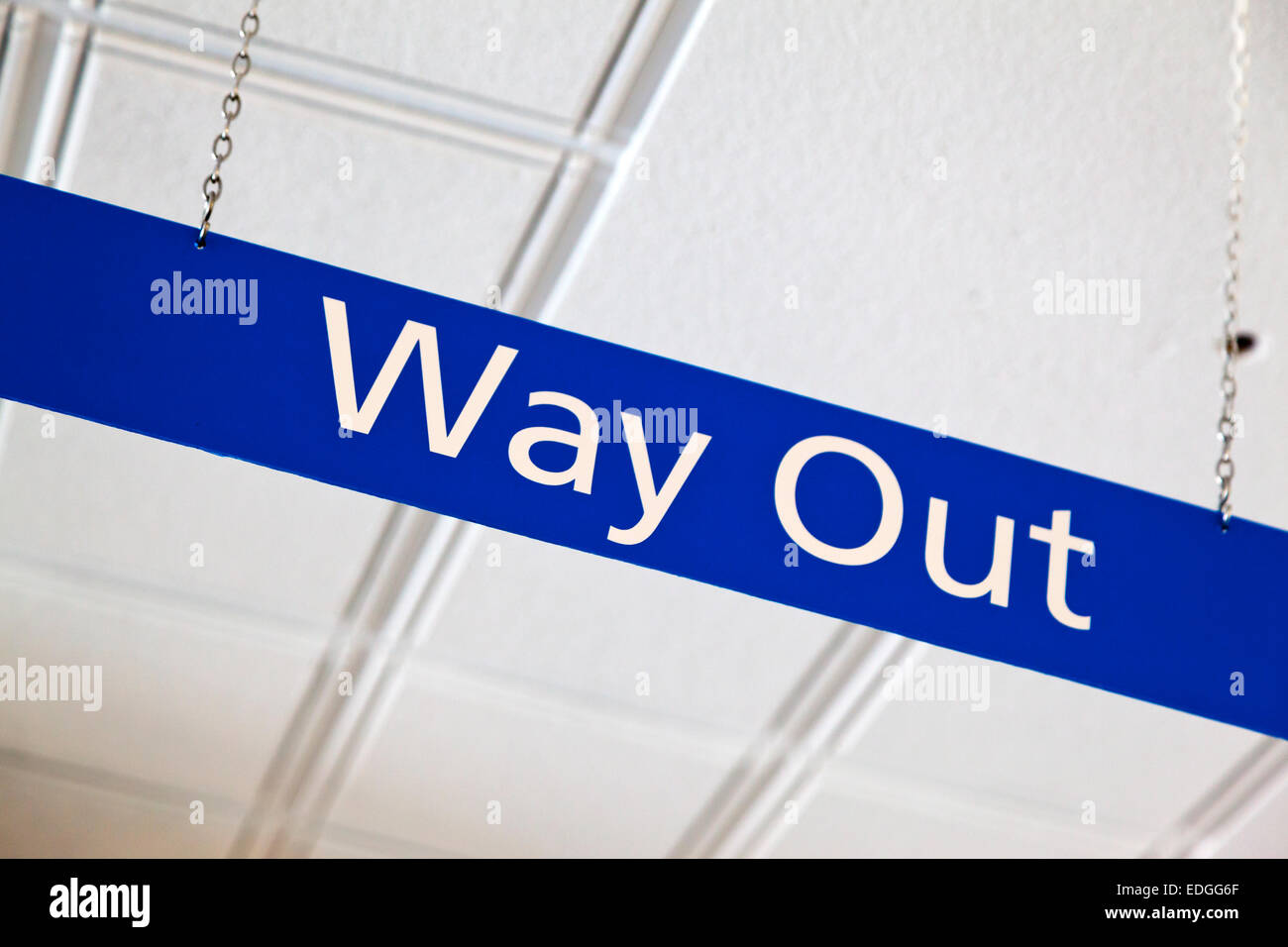 Blue Way Out sign hanging on a metal chain from the ceiling of a British National Health Service NHS hospital - Stock Image