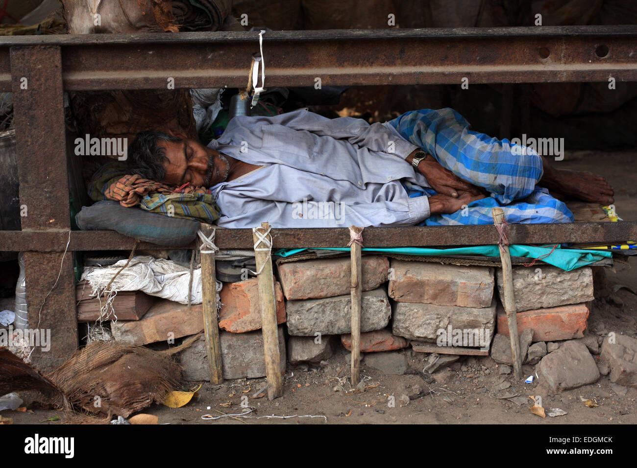 Homeless Indian man asleep beside the street in a ...