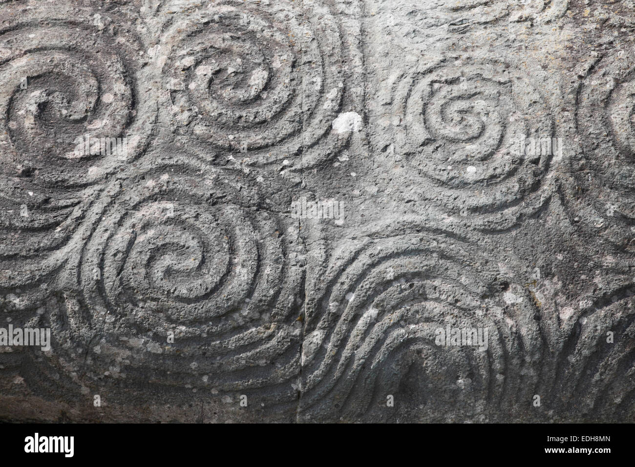 The Triple Spiral (Celtic symbol) engraved on a stone at the entrance of Newgrange, Bru na Boinne, County Meath, Stock Photo