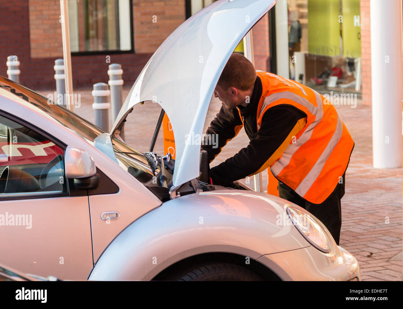Male mechanic working on a car with the bonnet (hood) up.  He is wearing an orange hi-viz jacket.  Inconvenient - Stock Image