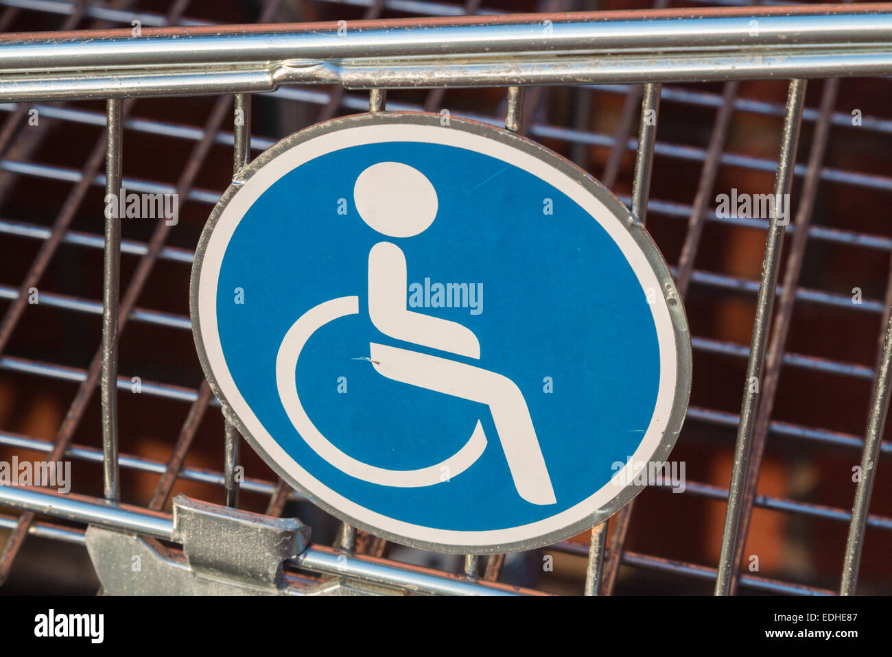 Wheelchair user disabled sign on a shopping cart /trolley extension for wheelchair users - Stock Image