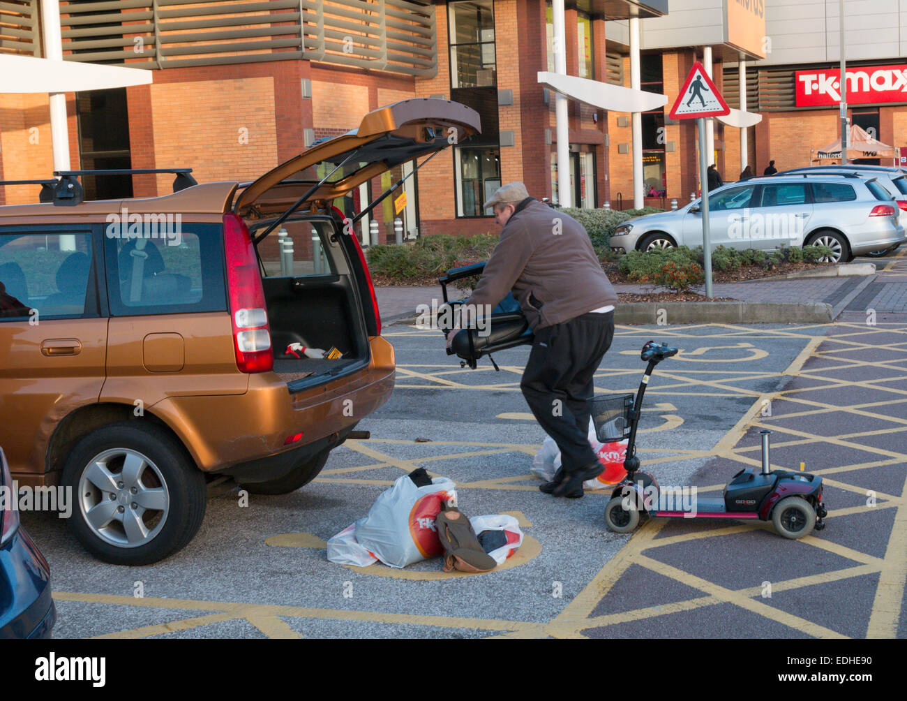 Man loading a disabled persons mobility scooter and bags into the back of a small hatchback car in a shopping centre - Stock Image