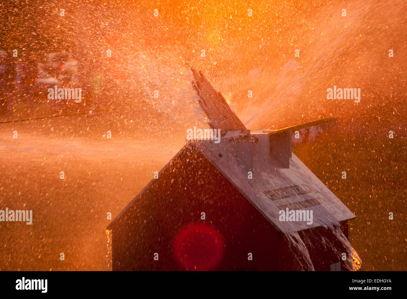 Water spray over a house fire demonstration with wooden flame for children to extinguish - Stock Image