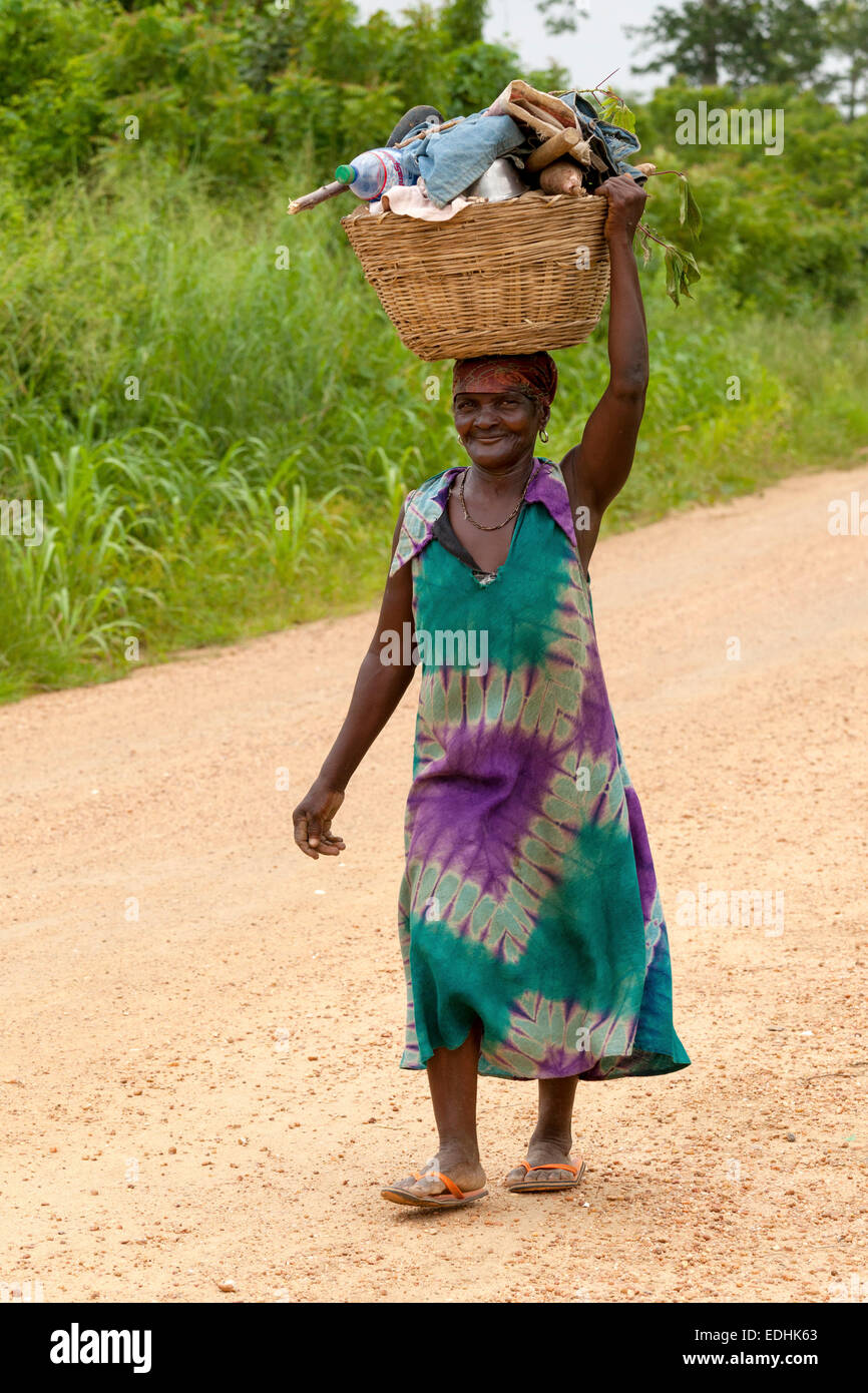 African woman carrying goods on head, rural Ghana, Africa - Stock Image