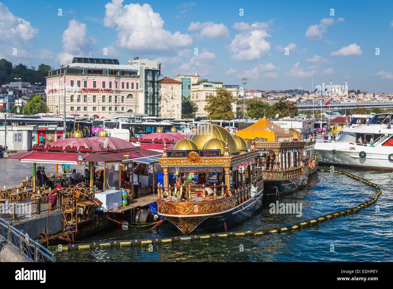 Eminonu Pier floating fish restaurants at the foot of the Galata Bridge in Istanbul, Turkey, Eurasia. - Stock Image