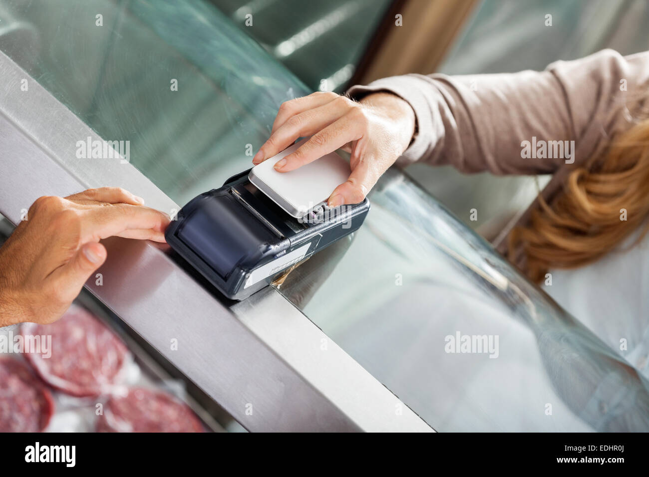 Customer Making Payment Through Smartphone In Butchery - Stock Image