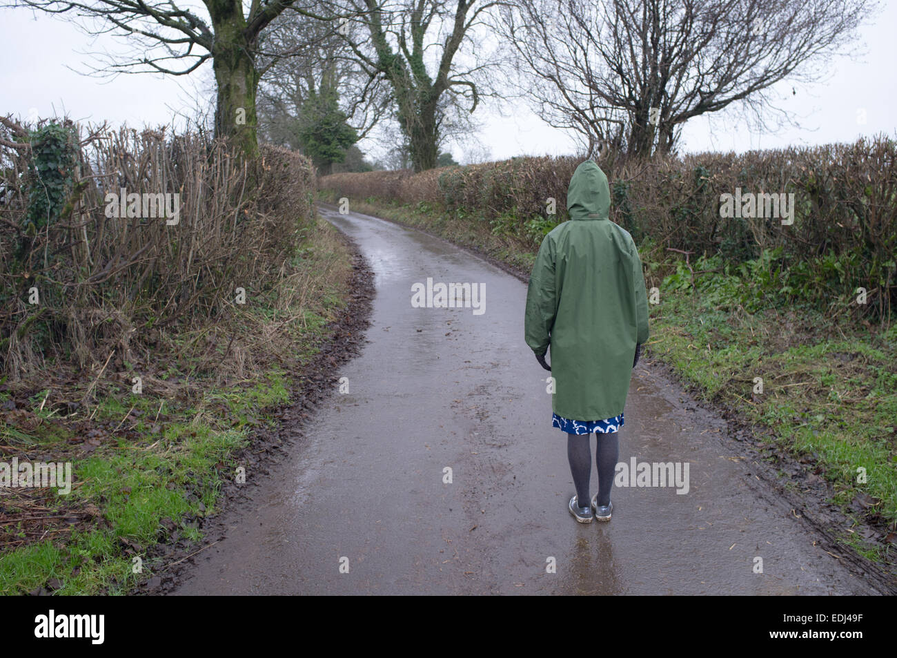A woman stands on a country lane - Stock Image