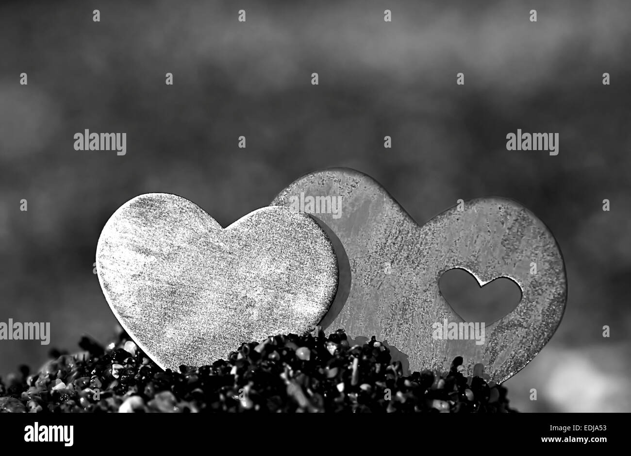 Two bright beautiful metal hearts are placed on top of a small sand hill. The background is diffuse beach and waves. Stock Photo