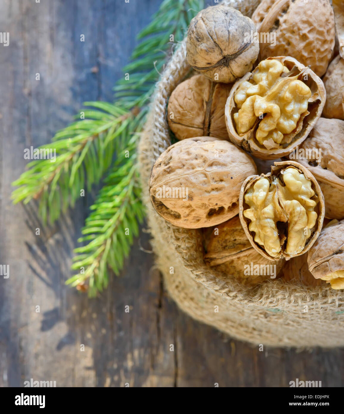 Christmas decoration with dried walnut in sack and pine tree twigs - Stock Image